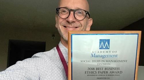 Andrew Crane holds up his 2018 Best Buisness Ethics Paper Award